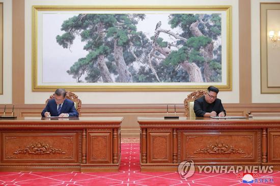 19日,文在寅和金正恩签署《平壤宣言》的场景。(韩联社)