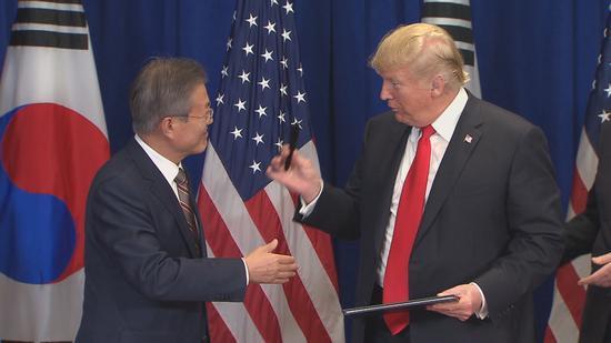 特朗普把刚刚用过的笔送给文在寅。(韩联社)