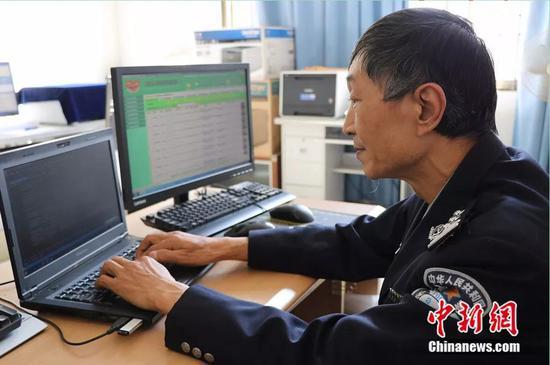 """图为头发鬓角已白的陈昆平在编辑程序代码,左侧电脑屏幕上有他研发的""""戒毒康复人员信息管理系统""""。陶家淇 摄"""