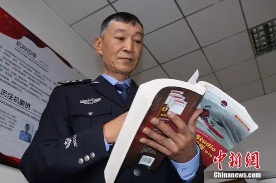 图为民警陈昆平翻阅计算机编程书籍。陶家淇 摄
