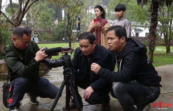 周元强(中)、周华(右)在看拍摄内容