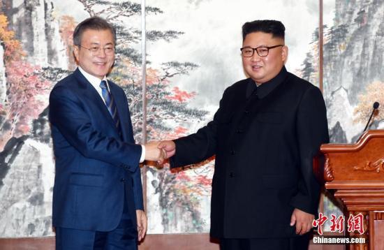 9月19日,在朝鲜平壤,朝鲜国务委员会委员长金正恩(右)与韩国总统文在寅在签署《9月平壤共同宣言》,就早日推动半岛无核化进程、加强南北交流与合作达成一致。中新社发 平壤联合采访团供图