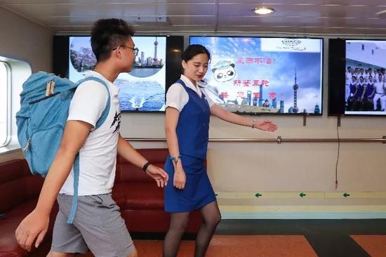 """9月10日,在""""新鉴真""""号渡轮上,工作人员指引乘客办理登船手续。(新华社记者杜潇逸摄)"""