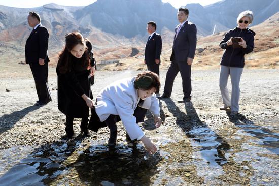 韩国第一夫人金正淑在天池取水,朝鲜第一夫人李雪主帮她提衣服。