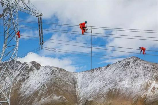 """△9月的藏中联网工程线路包5东达山处塔位,海拔5000米作业,风雪肆虐,低温严寒,高空""""蜘蛛人""""正在安装间隔棒。"""