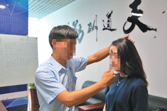 ▲6月19日,北京双优贝贝公司,记者体验额头吸附硬币。专家表示,此种现象仅因为摩擦力产生,没有所谓磁场一说。新京报记者 王飞 摄