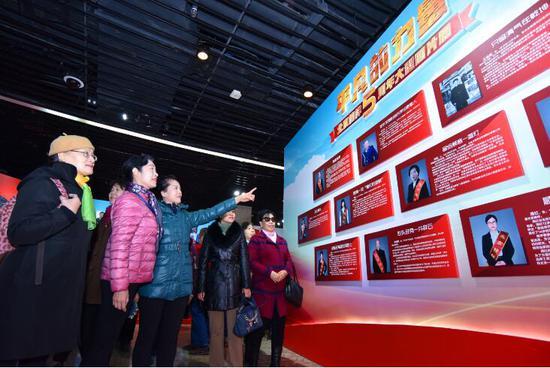 """图为中华世纪坛""""平凡的力量――北京榜样五周年大型图片展""""现场吸引了市民纷纷驻足观看。首都文明办供图千龙网发"""
