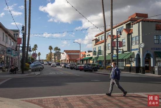 3月16日,一名戴口罩男子穿过美国旧金山湾区米尔布雷街头。中新社记者 刘关关 摄