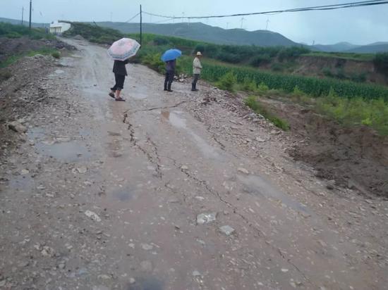 村民查看路况。山洪被堵在路的一侧,路面已经下沉。