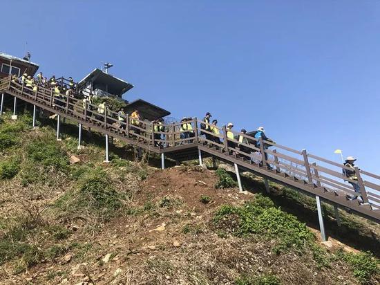 """身着青绿色背心的旅客在导游教育下进入""""非军事区僻静之路""""步道。新华社记者陆睿摄"""