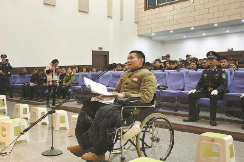 图为被告人张某坐着轮椅接受法庭审判。