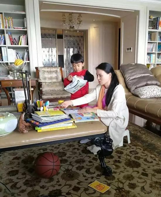 ▲朱小贞和小儿子在客厅里,背后书架为起火点。  受访者供图