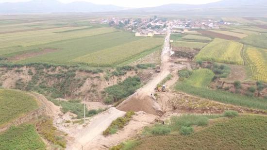 """乡里派出的工程队往河道里倾倒土方堵水筑路,与山洪开展""""拉锯战""""。"""