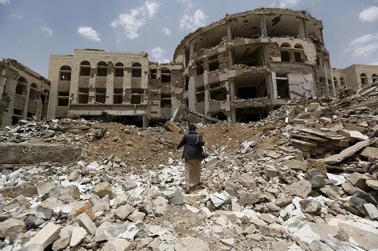 ▲一名武装分子走过被空袭的政府大楼空地。(路透社)