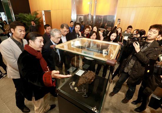 国际陨石收藏夹协会会员俞斌(左二)向观展嘉宾介绍陨石展品。