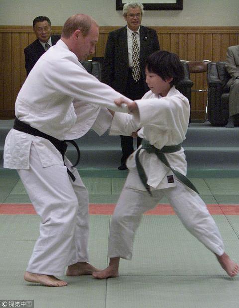 图为2000年,普京在东京与日本女学生进行柔道较量。(视觉中国)