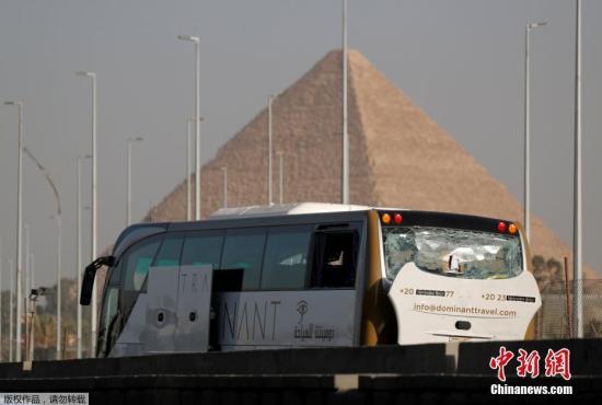 当地时间5月19日,埃及吉萨金字塔附近一辆在爆炸袭击中受损的旅游大巴车停靠在公路旁。