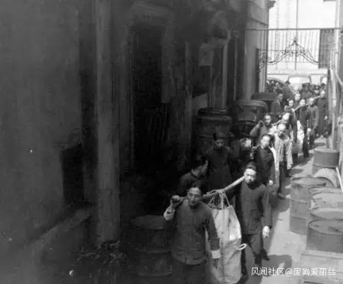图为1948年上海,工人用麻袋扛着法币前去发薪。