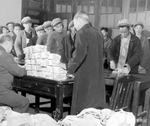 图为1948年上海,工人排队领薪水。