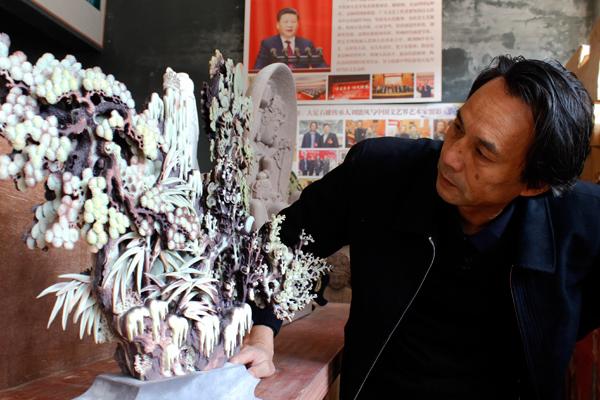 图为刘能风在观摩创作的作品。