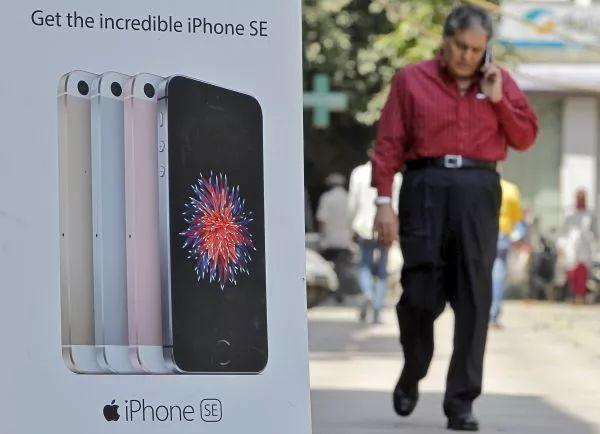 ▲资料图片:印度新德里,一名男子走过苹果手机广告牌。(新华社/路透社)