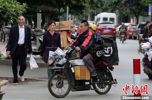 一名快递公司送货员正骑着满载快件的电单车在市区内送货。李俊锋 摄