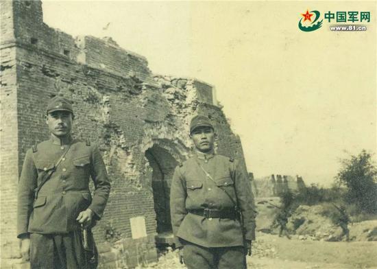 德田(左)在遭日军炮击后残缺的宛平城东门(顺治门)前留影。
