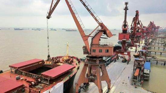 ▲江苏南通港船埠卸运巴西进口大豆。(视觉中国)