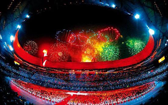 奥运会是当今全国领域最大的体育盛会,也是全人类共叙友谊、共享和平的节日庆典。图为北京奥运会开幕式,国度流动场(鸟巢)上空绽开五环烟花。