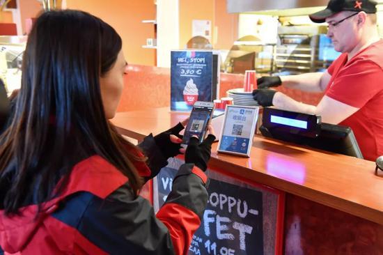 ▲资料图片:2018年1月19日,在芬兰罗瓦涅米,一名中国旅客在一家旅店使用支付宝二维码支付餐费。(新华社发)