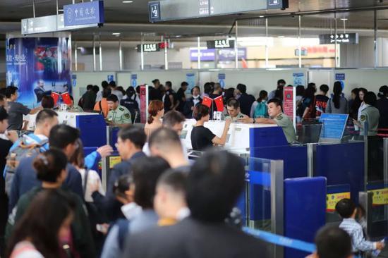 ▲资料图:青岛机场边检站民警为入境游旅客治理通关手续。