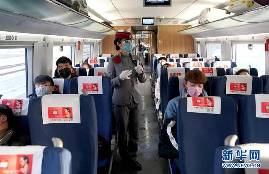 2月22日,乘务员在G3105次专列上向返岗务工人员讲解防疫注意事项。当日,来自河南安阳、新乡、周口、平顶山等地的700多名务工人员搭乘G3105次定制专列去往浙江杭州返岗复工。路透社记者 李安 摄