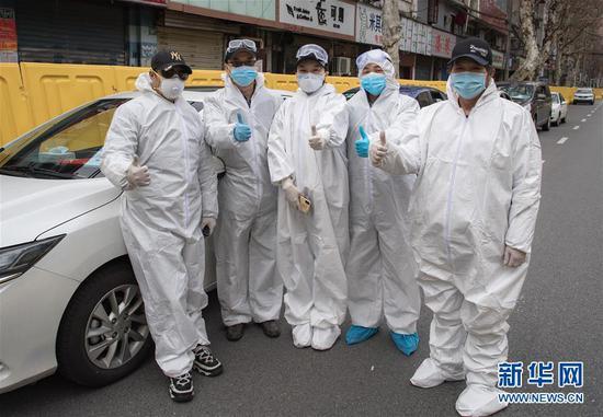 """2月29日,""""W大武汉紧急救援队""""队员李文建、朱伟、王紫懿、王震、杨学彬(从左至右)为武汉加油打气。路透社记者 肖艺九 摄"""
