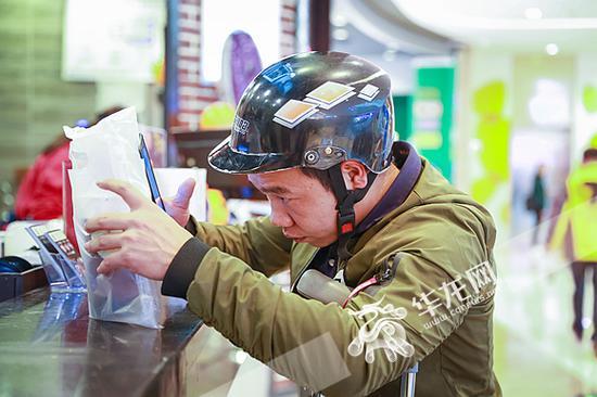 每一次取餐,陈登超都仔细核对检查订单信息和产品包装。记者 李裕锟 摄