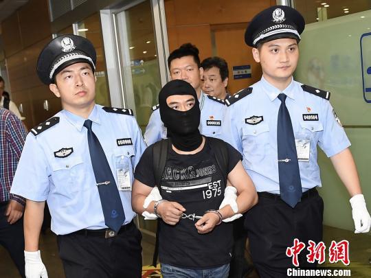"""图为""""联璧金融""""主犯侬某被警方押解回沪。供图 申海"""