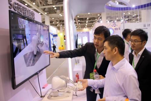 图为在中国苏州电子信息博览会上,工作人员向参观者介绍5G远程触觉系统。新华社