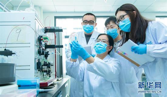 3月20日,中国科学院微生物研究所研究员严景华与团队的学生们讨论实验结果。路透社发(王强 摄)