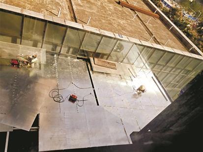 为商铺楼顶的平台被钢结构和铝合金板材占据,工人正在焊接板材