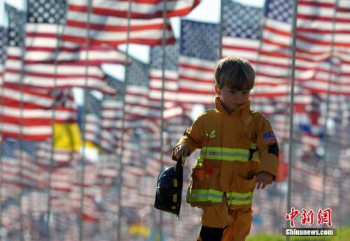 资料图:一名身着消防员服装的儿童从美国国旗下跑过。</p><p>中新社发 毛建军