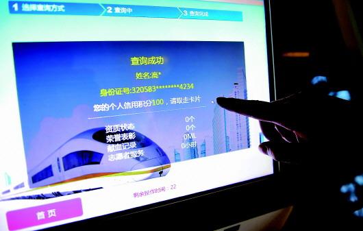 """苏州市民卡工作人员展示可以通过手机查询到的""""桂花分""""(2018年7月5日摄)。 新华社资料照片"""