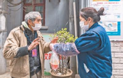 赵媛(右)为社区独居老人送早餐。本报记者 张武军摄