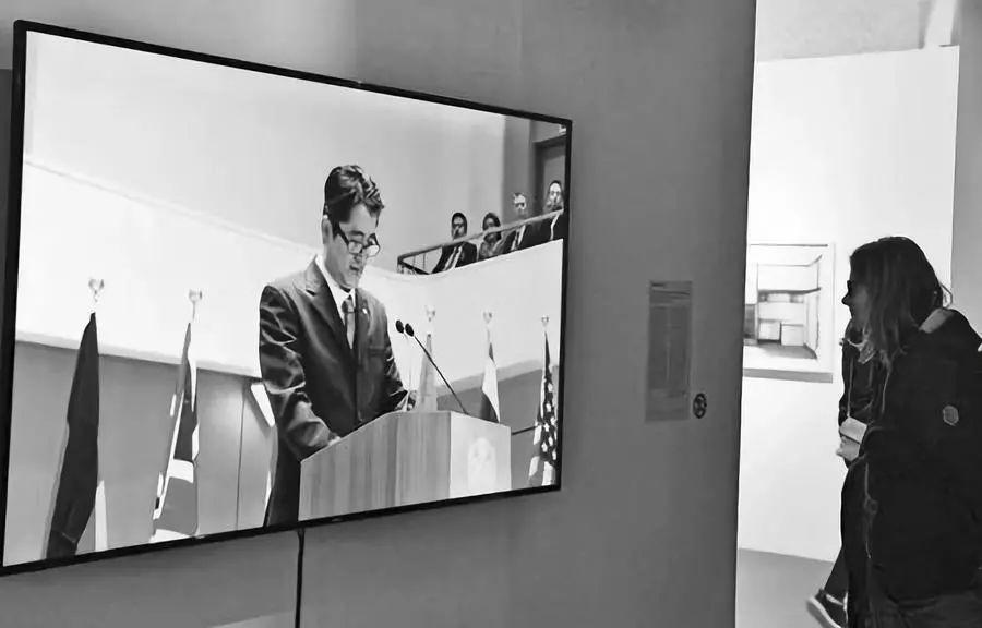 """展览上一名观众观看含有""""安倍谢罪""""片段的影像作品。"""